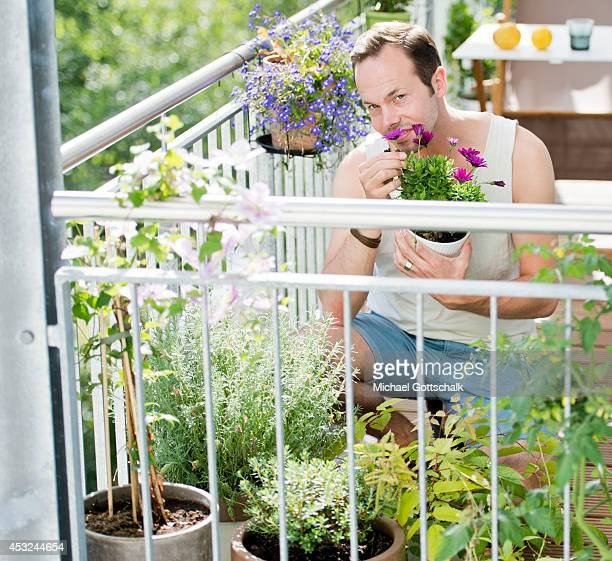A young man smelling at a plant on the balcony on July 03 2014 in Berlin Germany