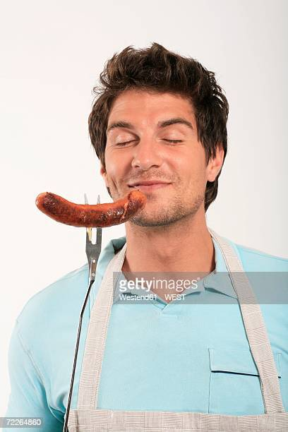 Young man smelling grilled sausage on fork, eyes closed, close-up