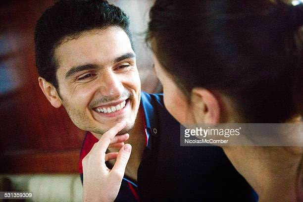 Young man smiles as his girlfriend caresses his chin
