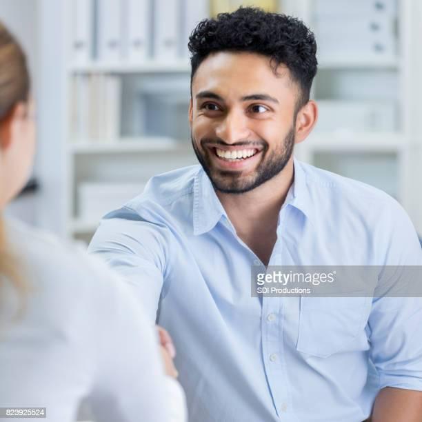 Junger Mann lächelt breit als He schüttelt Hände mit neuen Arbeitgeber