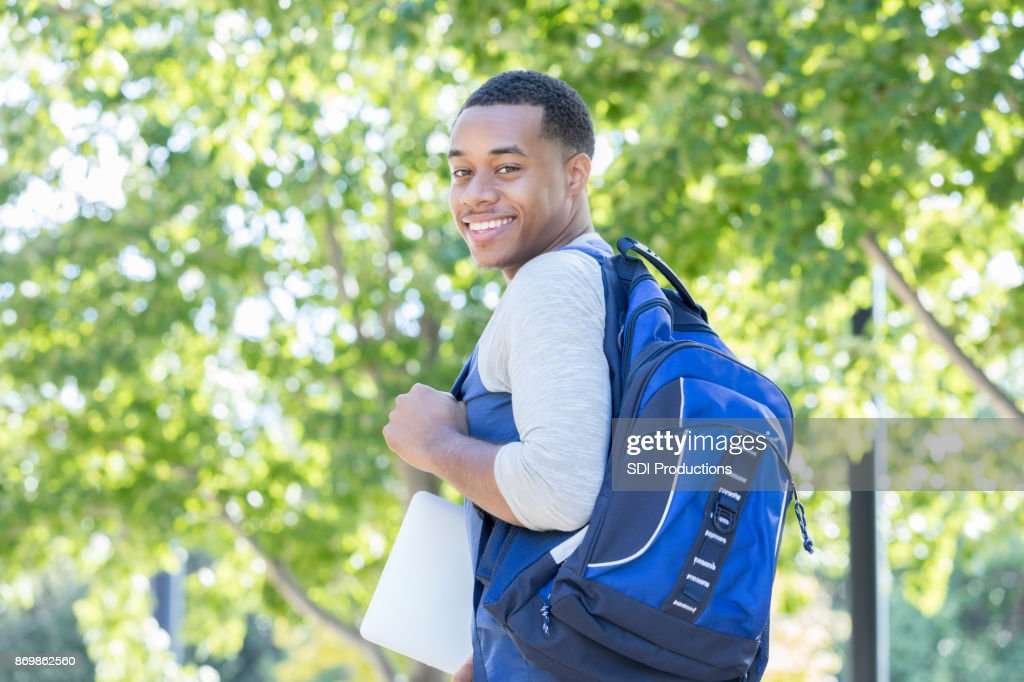 Young man smiles for camera on first day of college : Stock Photo