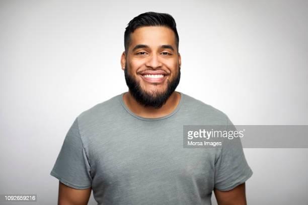 young man smiling against white background - nur erwachsene stock-fotos und bilder