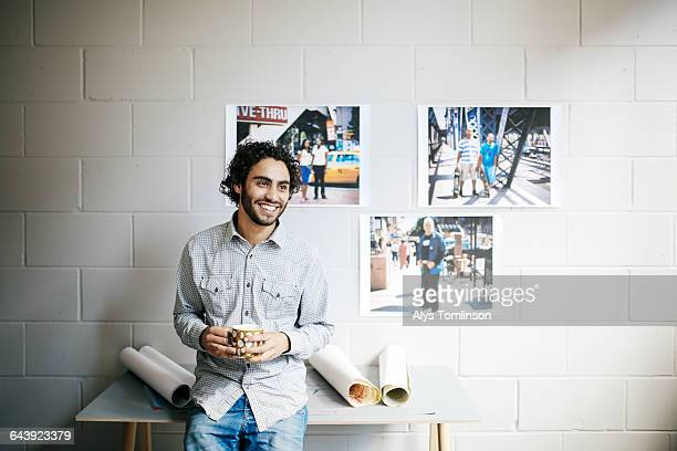 young man smiling and drinking coffee in studio