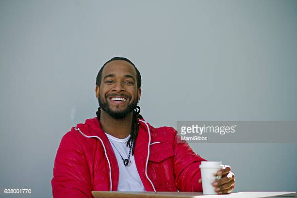 young man smiling and drinking coffee - rasta photos et images de collection
