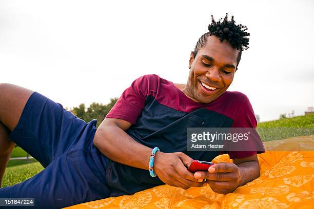 a young man smiling and using a cellular device. - rasta photos et images de collection