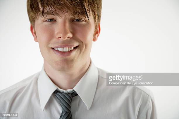 young man smiling and wearing shirt and tie