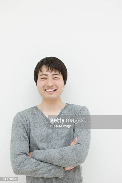 Young man smiling, arms crossed