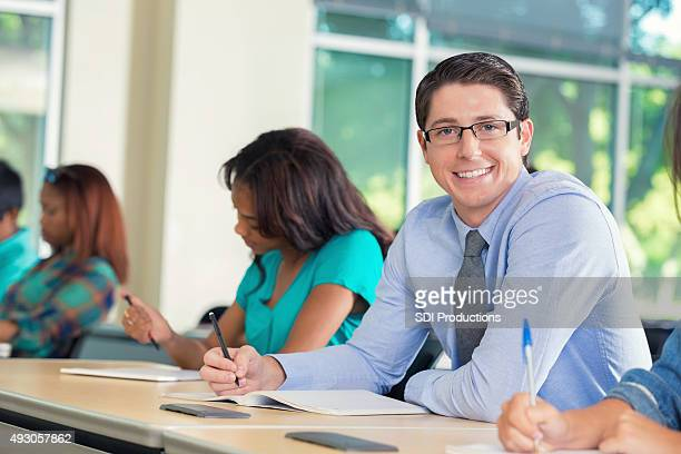 Young man smiling at camera during college class