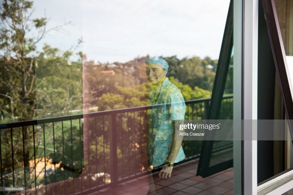 Young man smiling at window : Stock Photo