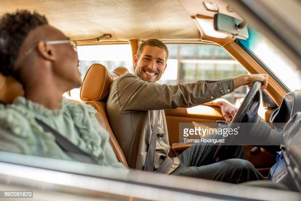 young man smiling at woman inside of car - friends inside car stock photos and pictures