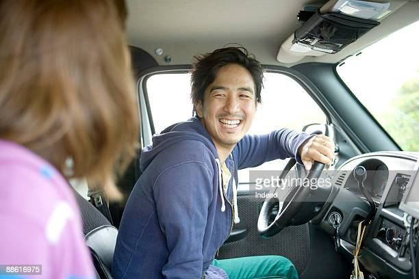 Young man smiling at young woman in car