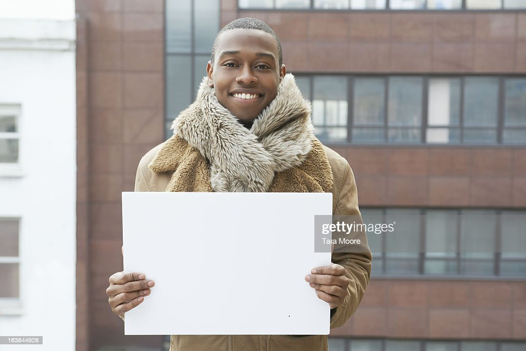 young man smiling blank sign : Stock-Foto