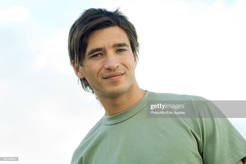 Young man smiling outdoors, portrait : Stock Photo