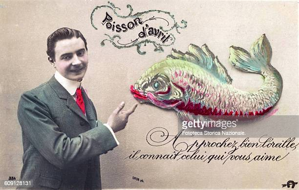 Young man smiling pointing a big fish with his finger Around the playful animal it reads Poisson d'avril Approcher bien l'oreille il connait celui...