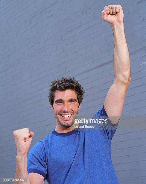 Young man smiling,  raising fists in air