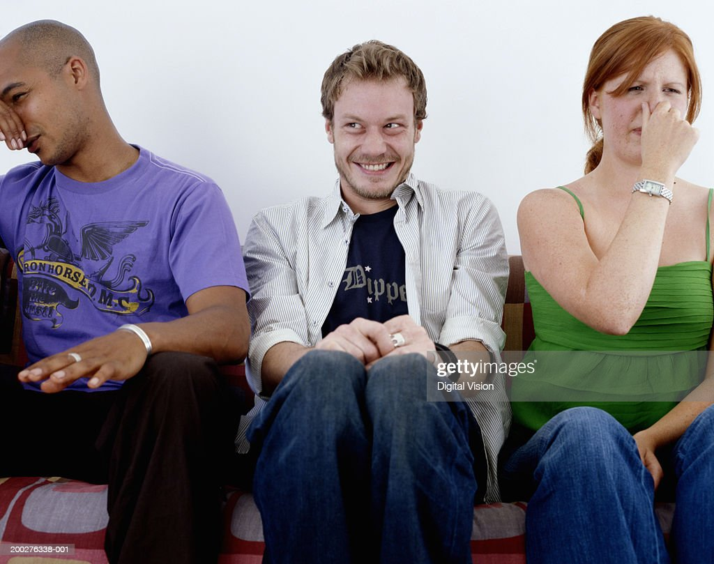 Young man, smiling, sitting between man and woman holding noses : Stock Photo