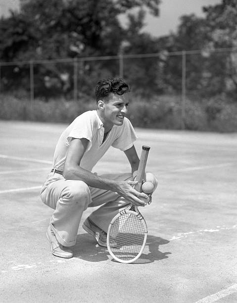 Young Man Smiling Squatting Holds Tennis Racquet And...