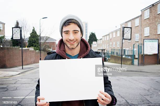 young man smiling to camera holding blank sign - blank sign stock photos and pictures