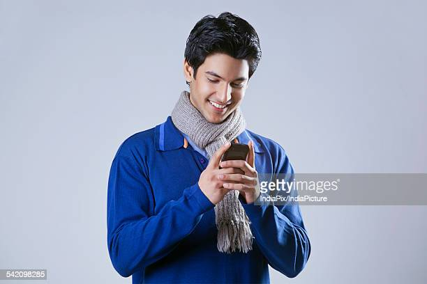 Young man smiling while reading text message
