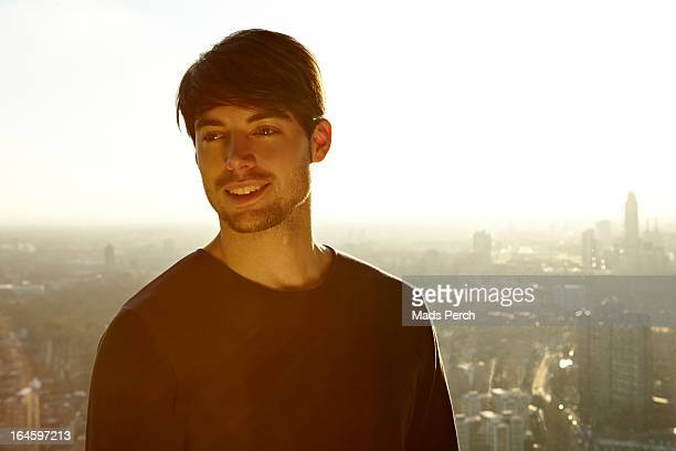 young man smiling with city view behind him