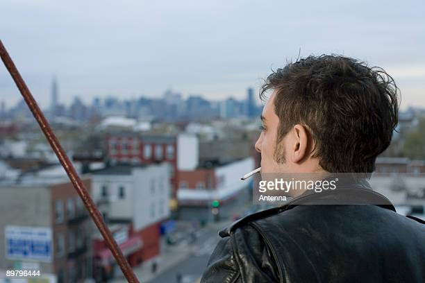 a young man smoking a cigarette on a fire escape - sideburn stock pictures, royalty-free photos & images