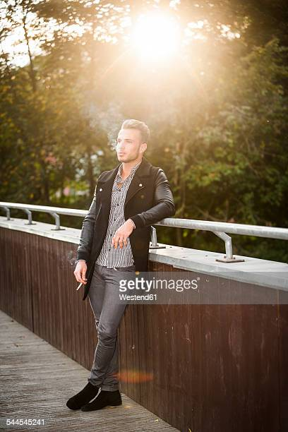 Young man smoking a cigarette on a footbridge at backlight