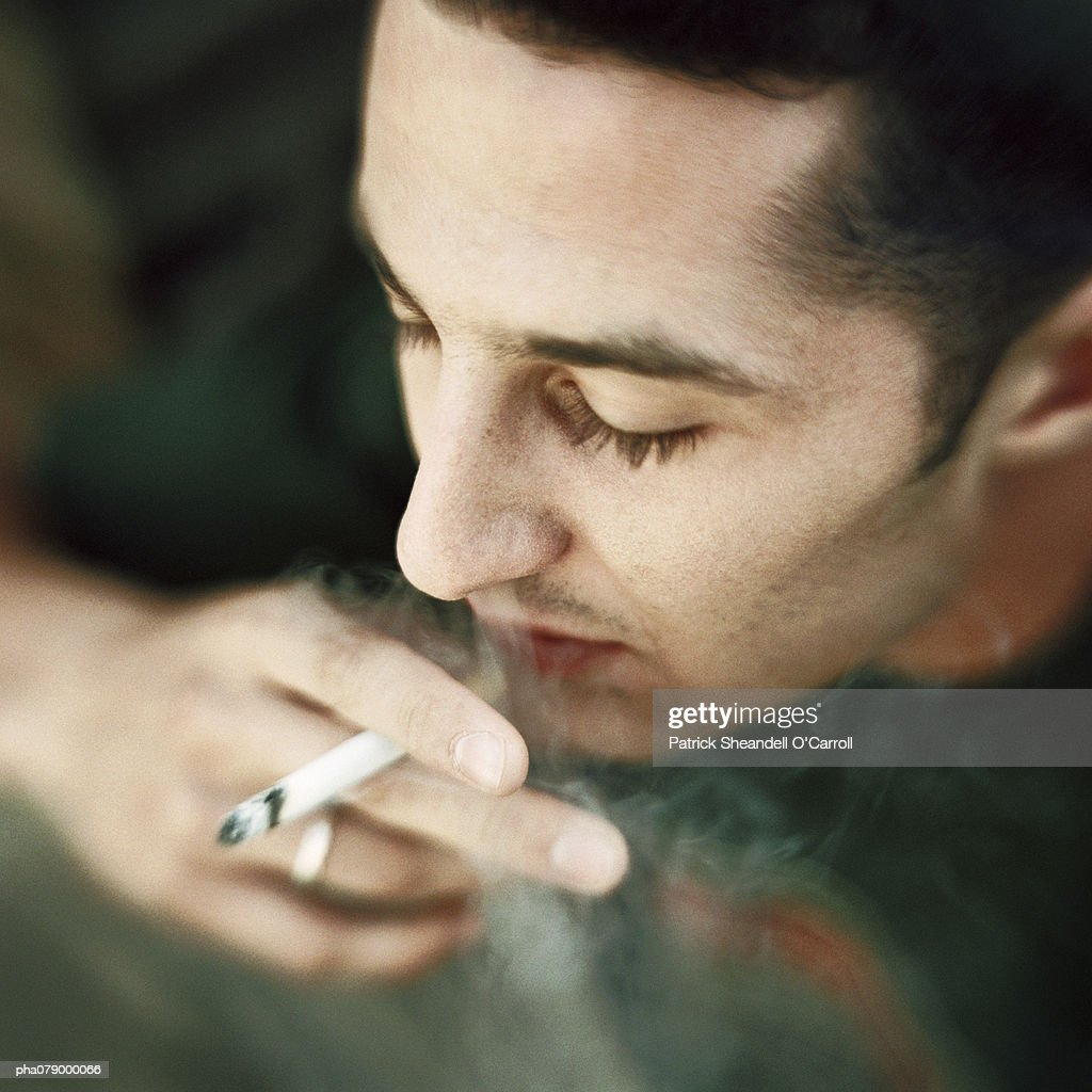 Young man smoking a cigarette, view from above, portrait. : Stockfoto