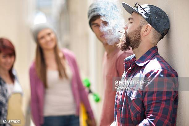 Young man smoking a cigarette with friends in background