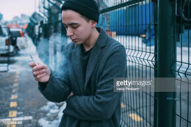 Young man smoking along winter fence
