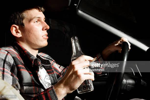 Young man smoking and drinking alcohol while driving