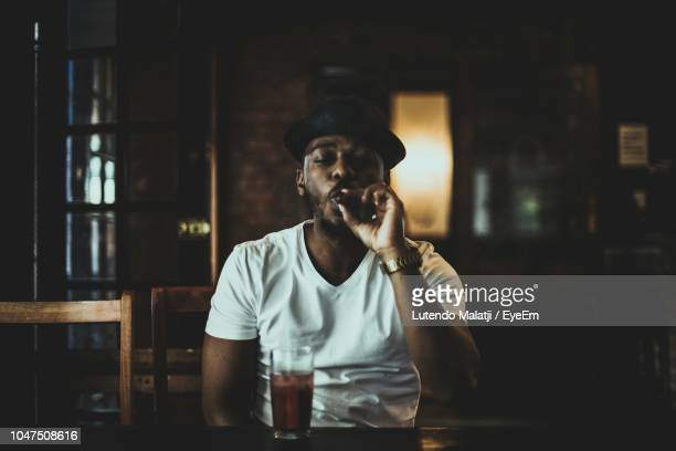 young man smoking cigar while sitting on table at bar - cigar stock pictures, royalty-free photos & images