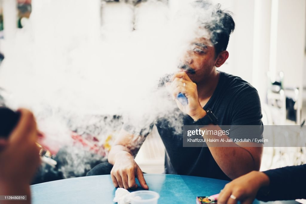 Young Man Smoking Electronic Cigarette While Sitting At Table : Stock Photo