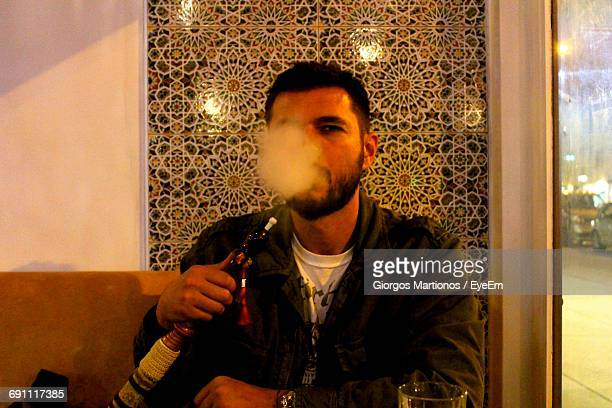 young man smoking hookah against wall - chicha photos et images de collection