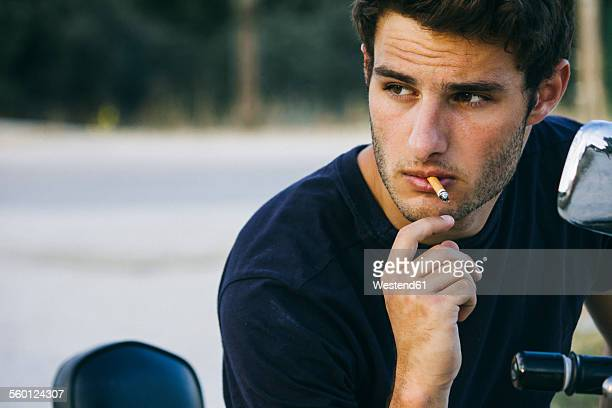 Young man smoking sitting on his motorbike