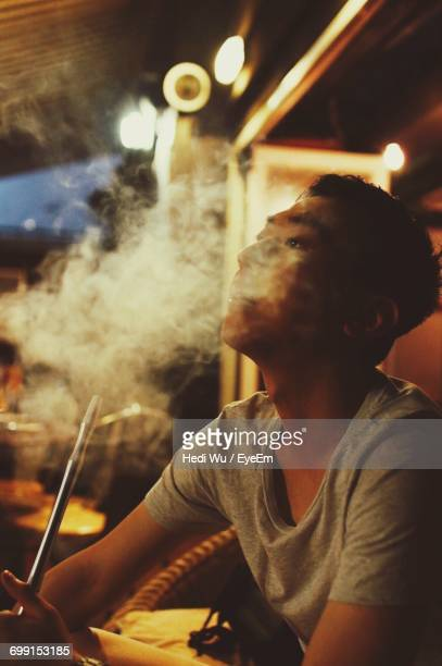 young man smoking while sitting in bar - 水キセル ストックフォトと画像