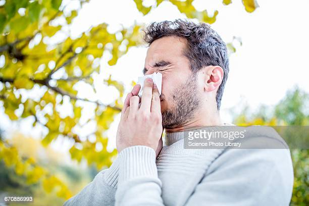 young man sneezing - allergies stock photos and pictures