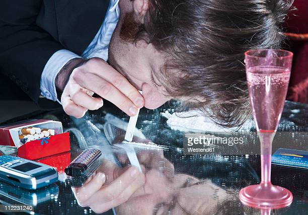 young man sniffing cocaine - cocaine stock photos and pictures