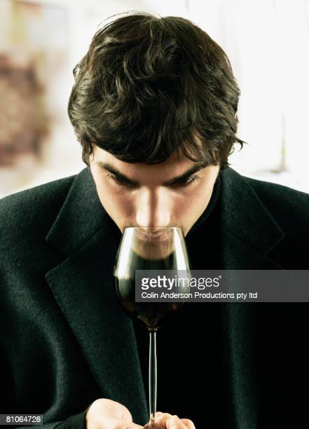 Young man sniffing glass of wine