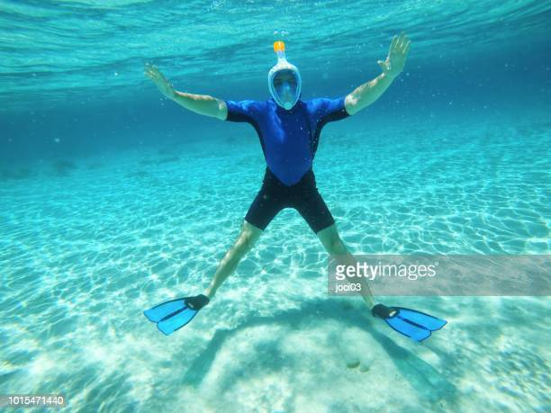 young man snorkeling in turquoise waters - glider stock photos and pictures