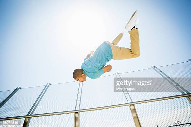 Young man somersaulting on a bridge.
