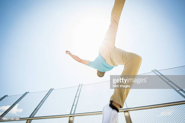 young man somersaulting on a bridge. - unusual angle stock pictures, royalty-free photos & images