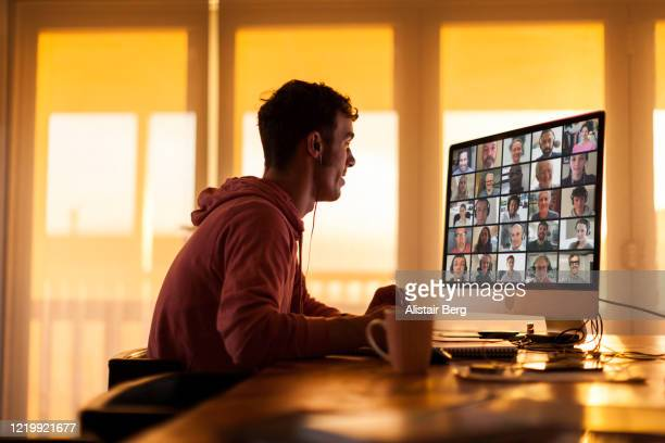 young man speaking to colleagues on video call from his home during lockdown - video conference stock pictures, royalty-free photos & images