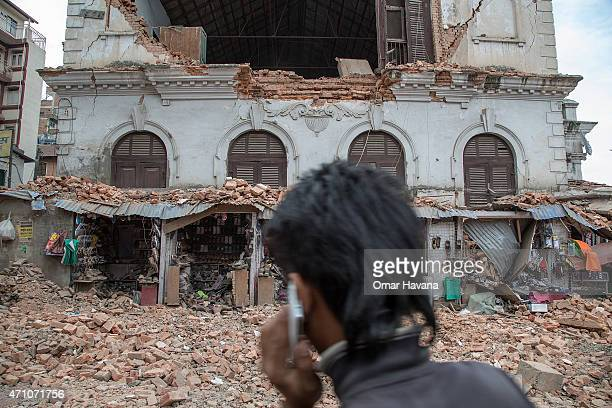 Young man speaks on the phone in front of a collapsed building in the city center following an earthquake on April 25, 2015 in Kathmandu, Nepal. A...