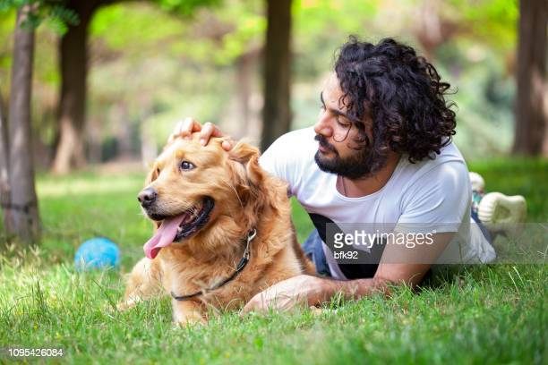 young man spending time with his golden retriever outdoors. - dog turkey stock pictures, royalty-free photos & images
