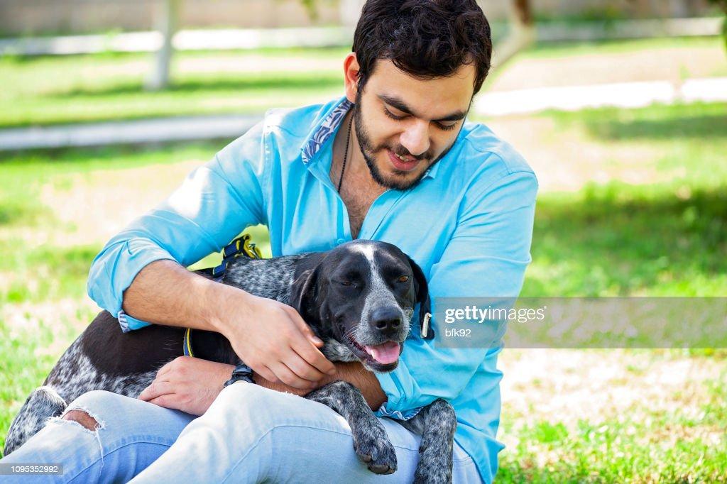 若者は彼のハンター犬を屋外で過ごす時間。 : ストックフォト