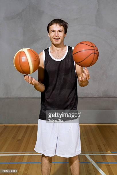 A young man spinning two basketballs on his fingers