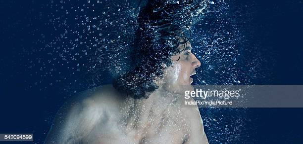 Young man splashing water from his wet hair while bathing