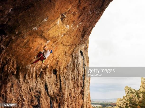 young man sport climbing in overhanging position - free climbing stock pictures, royalty-free photos & images