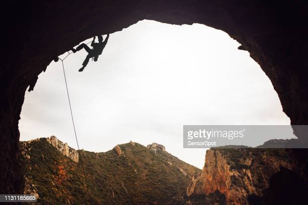 young man sport climbing in overhanging position - rock overhang stock pictures, royalty-free photos & images