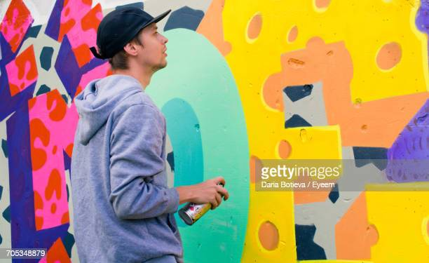 Young Man Spray Painting Wall